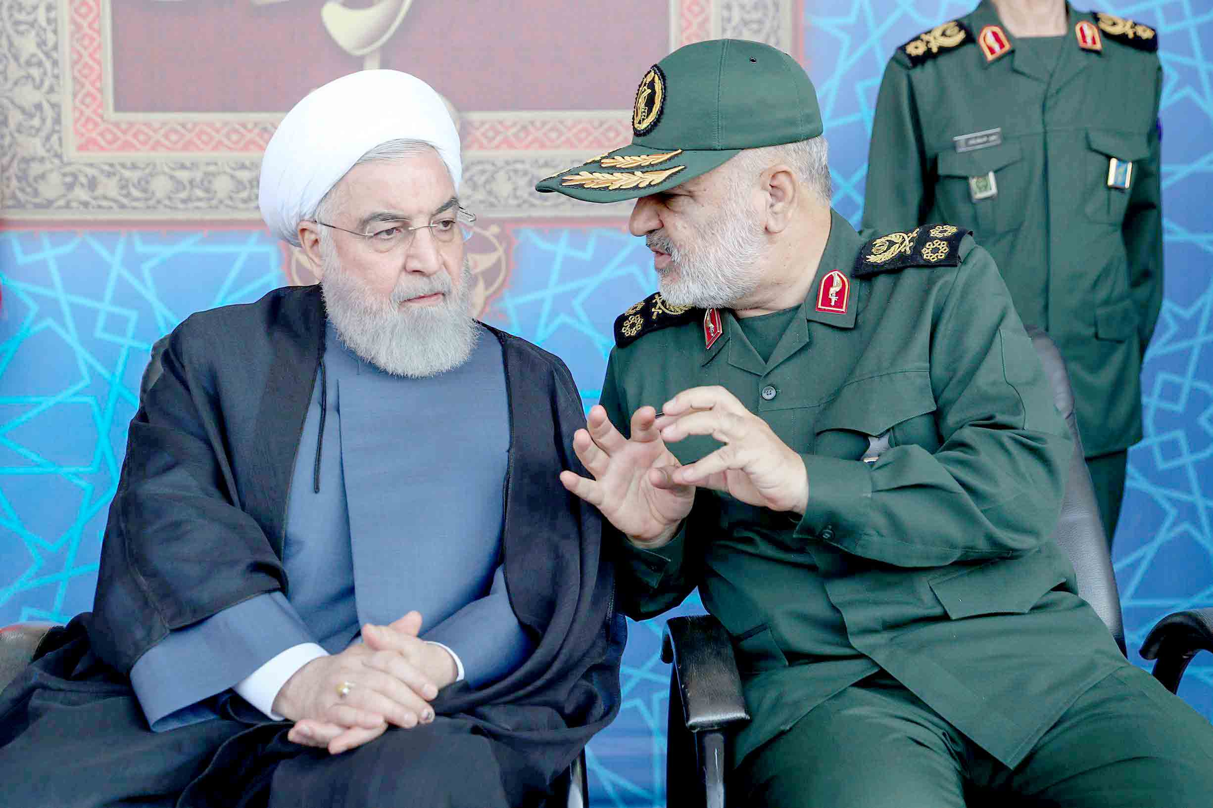 Brewing new plots? Iranian President Hassan Rohani (L) listens to Islamic Revolutionary Guard Corps Commander Major-General Hossein Salami as they attend a parade marking the anniversary of the outbreak of the devastating 1980-1988 war with Iraq, in Tehran, September 22.(AFP)