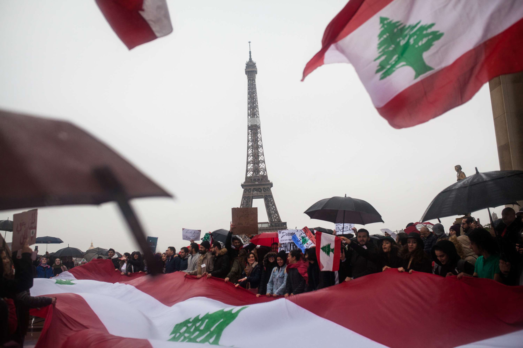 People shout slogans and wave Lebanese national flags as they take part in a rally in Paris to support Lebanon's protests, October 20. (DPA)
