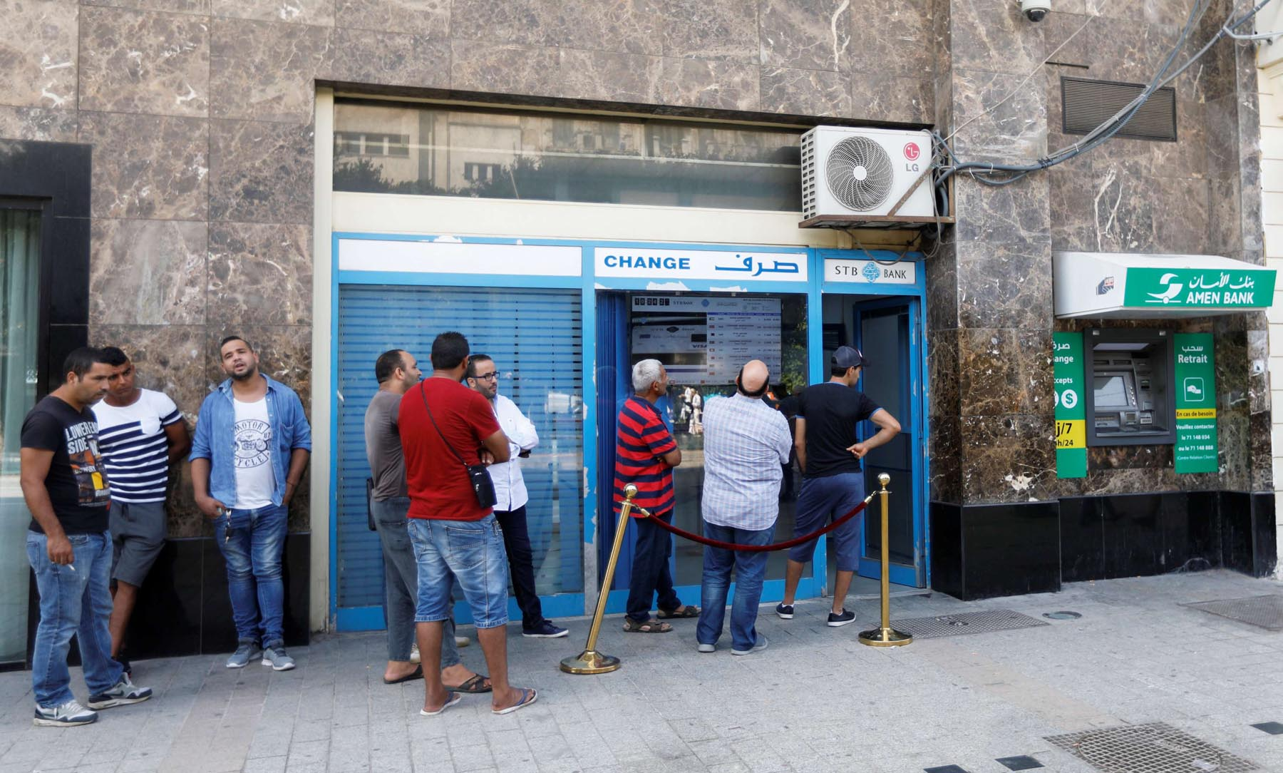 People change money at a currency exchange bank in Tunis.        (Reuters)