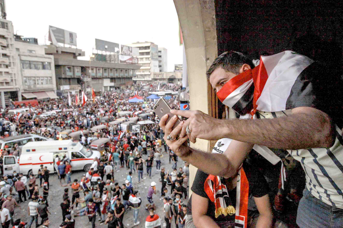 Defying the crackdown. An Iraqi demonstrator takes photos during an anti-government protest at Tahrir Square, November 1.  (DPA)