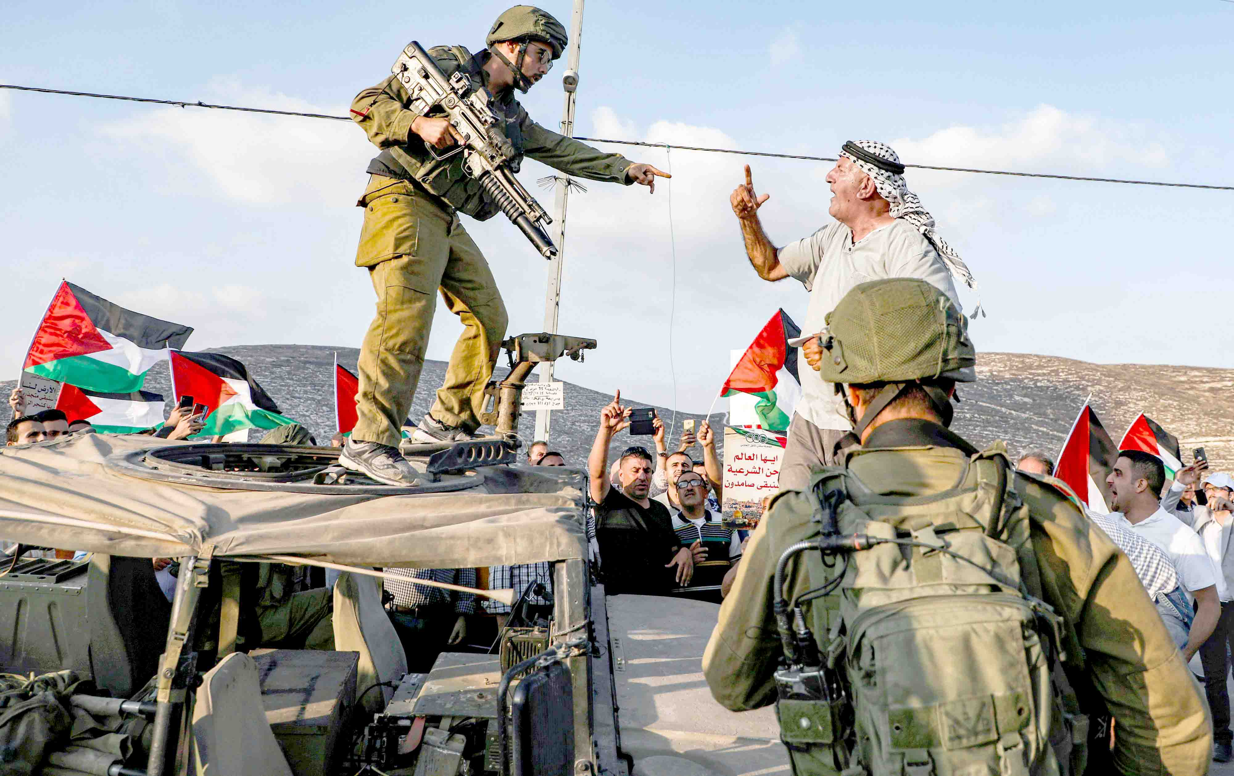 A Palestinian protester yells at an Israeli soldier during a protest in a residential area near the Palestinian village of Naqura, north-west of Nablus in the occupied West Bank, September 4. (AFP)