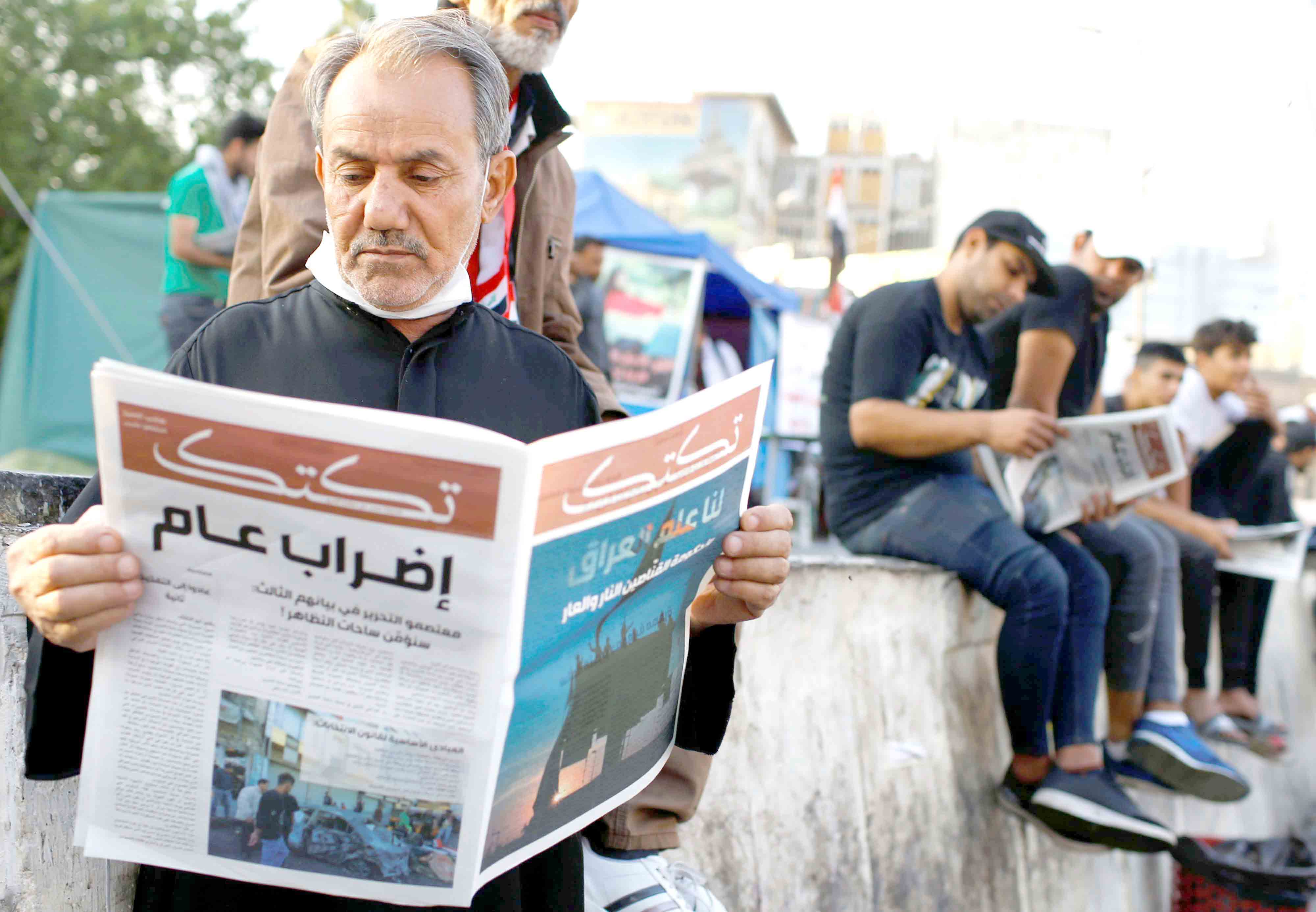 Bypassing the shutdown. An Iraqi demonstrator reads a copy of Tuktuk,  a newspaper that aims to be the voice of the largest grassroots protest, during anti-government protests in Baghdad, November 17.(Reuters)