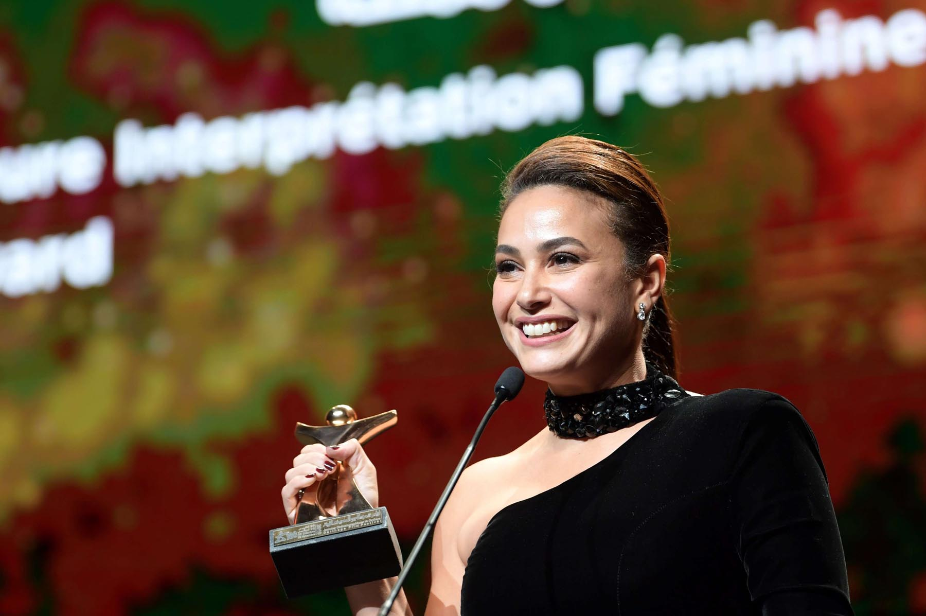 Tunisian actress Hend Sabry celebrates after receiving the Best Actress Tanit during the closing ceremony of the Carthage Film Festival, November 2.    (AFP)