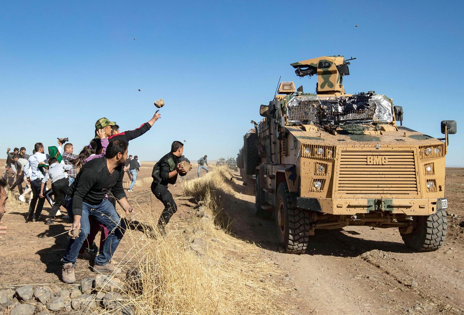 Kurdish demonstrators hurl rocks at a Turkish military vehicle during a joint Turkish-Russian patrol near the town of Al-Muabbadah in the north-eastern part of Hasakah on the Syrian border with Turkey, November 8. (AFP)