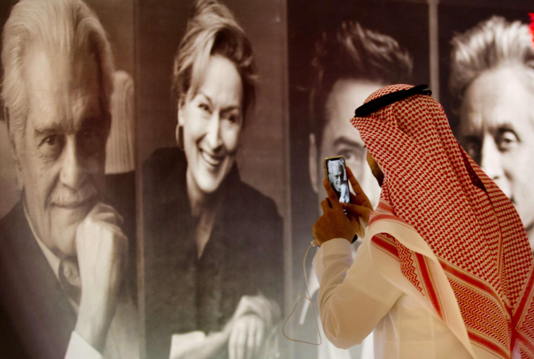 A visitor takes pictures of posters of Hollywood movie stars during a screening at the King Abdullah Financial District Theatre in Riyadh. (AP)