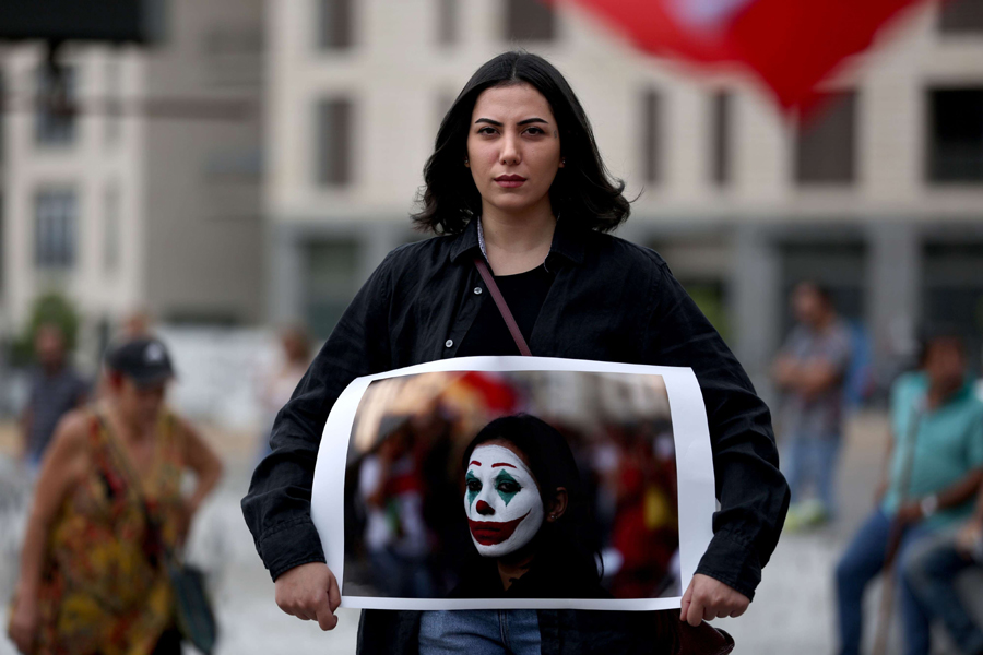 A Lebanese protester holds a picture of her face painted as the Joker in Beirut, October 23. (AFP)