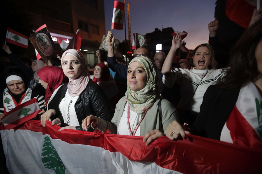 Lebanese protesters carry national flags as they take part in anti-government demonstrations in central Beirut, November 30. (AFP)