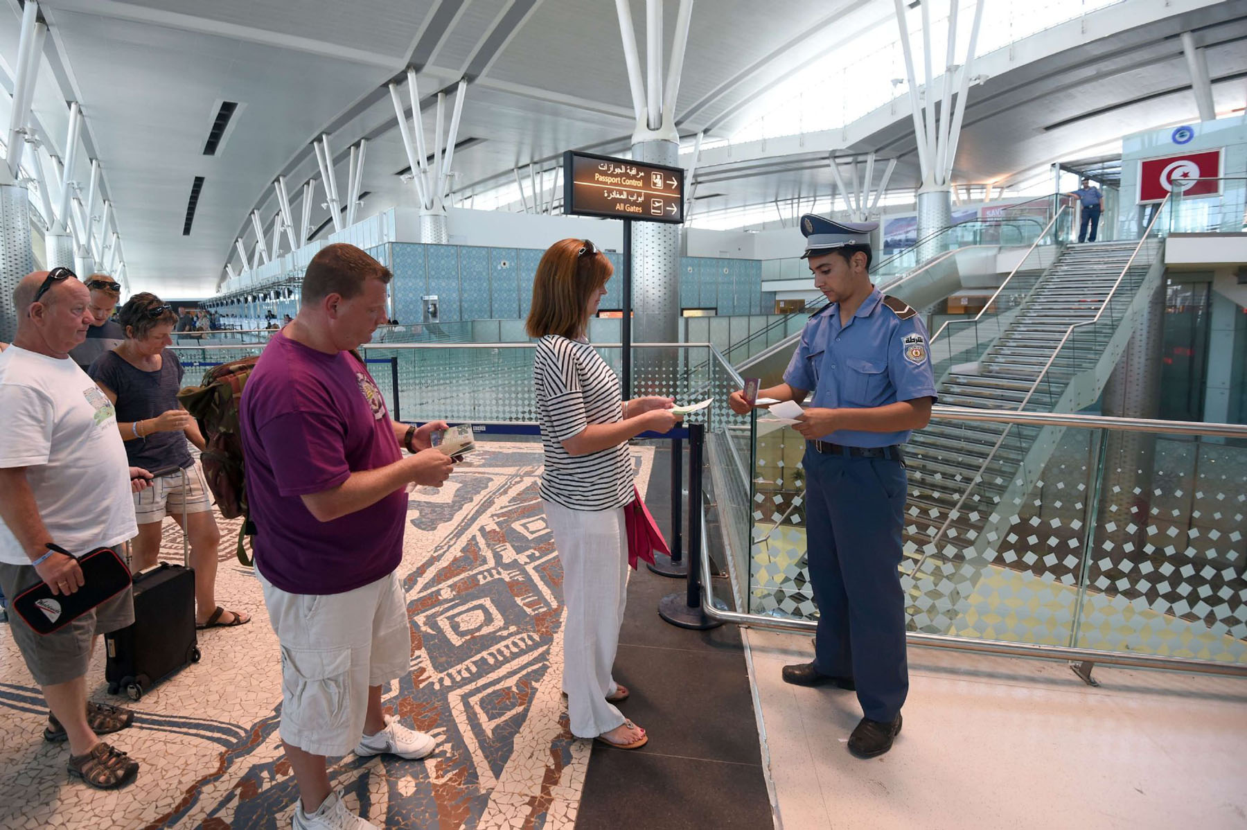 A Tunisian policeman checks tickets of British tourists leaving the country at the Enfidha International airport on June 27, 2015. (AFP)