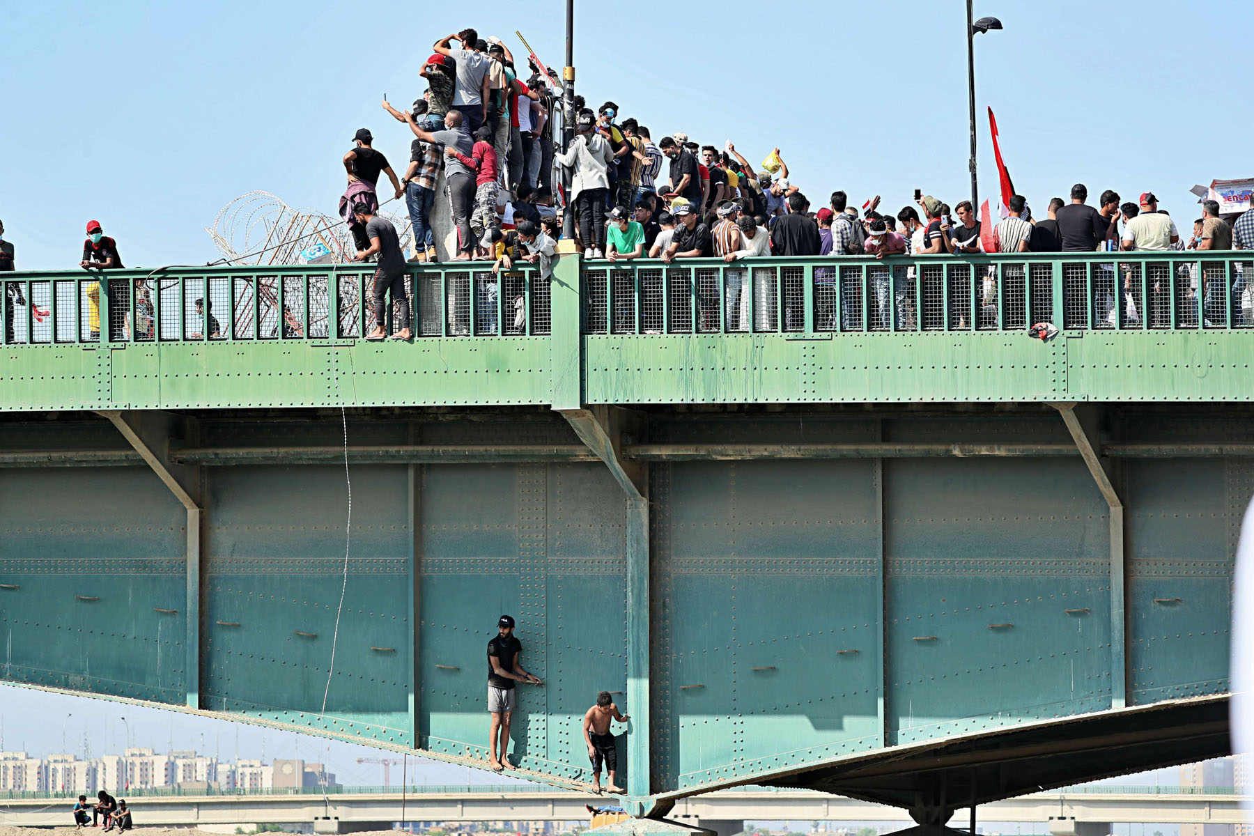 Anti-government protesters try to sneak past as security forces close the bridge leading to the Green Zone during a demonstration in Baghdad, Iraq, Saturday, October 26. (AP)