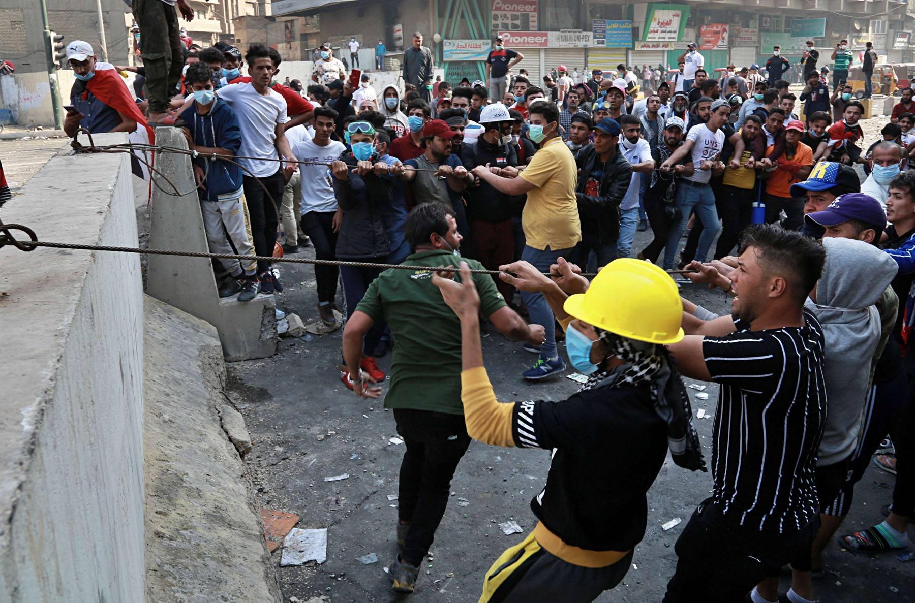 Protesters try to pull down concrete barriers during clashes with Iraqi security forces in Baghdad, November 10. (AP)