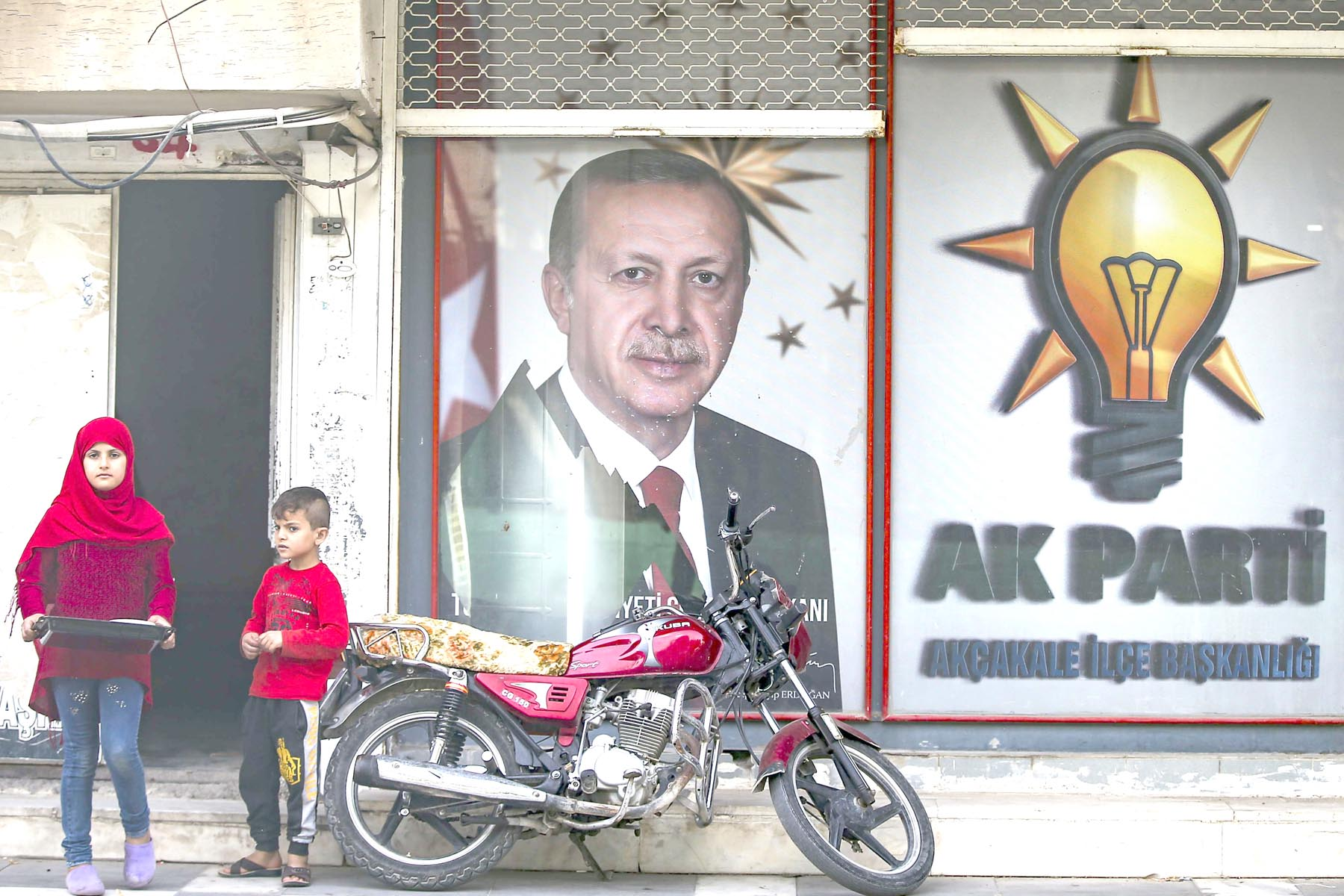 Autocratic slide. Turkish children stand in front of a billboard with a picture of Turkey's President Recep Tayip Erdogan and a poster of his ruling Justice and Development Party, AKP, in the border town of Akcakale, last October. (AP)