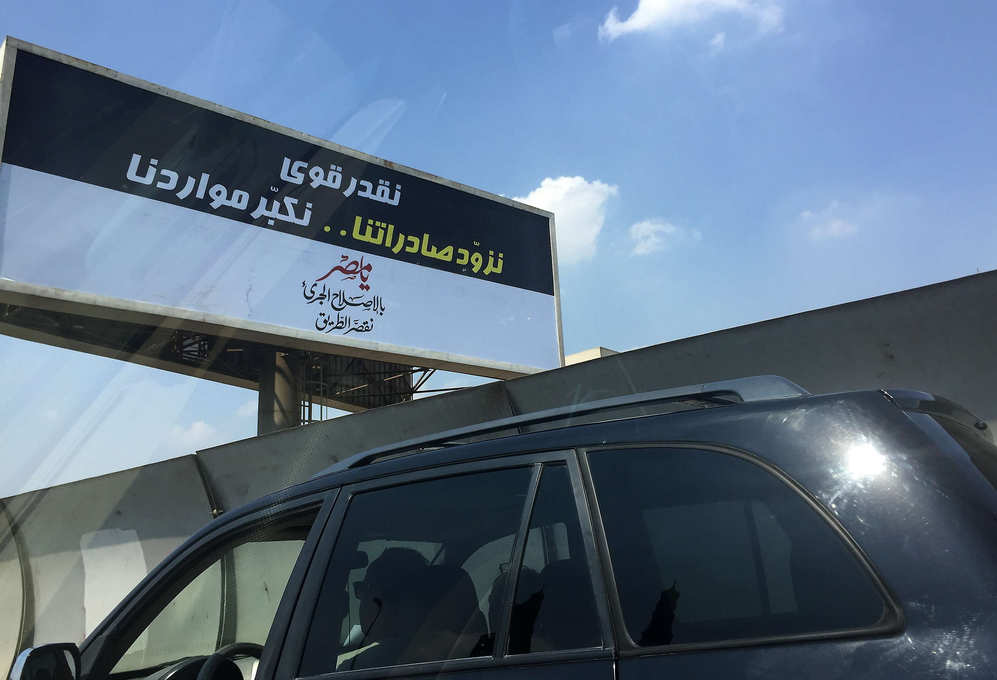 "A motorist drives past a government billboard in Cairo that reads in Arabic: ""We sure can ... boost our exports and increase our resources. Oh, Egypt, With bold reforms, we shorten the road."" (AP)"