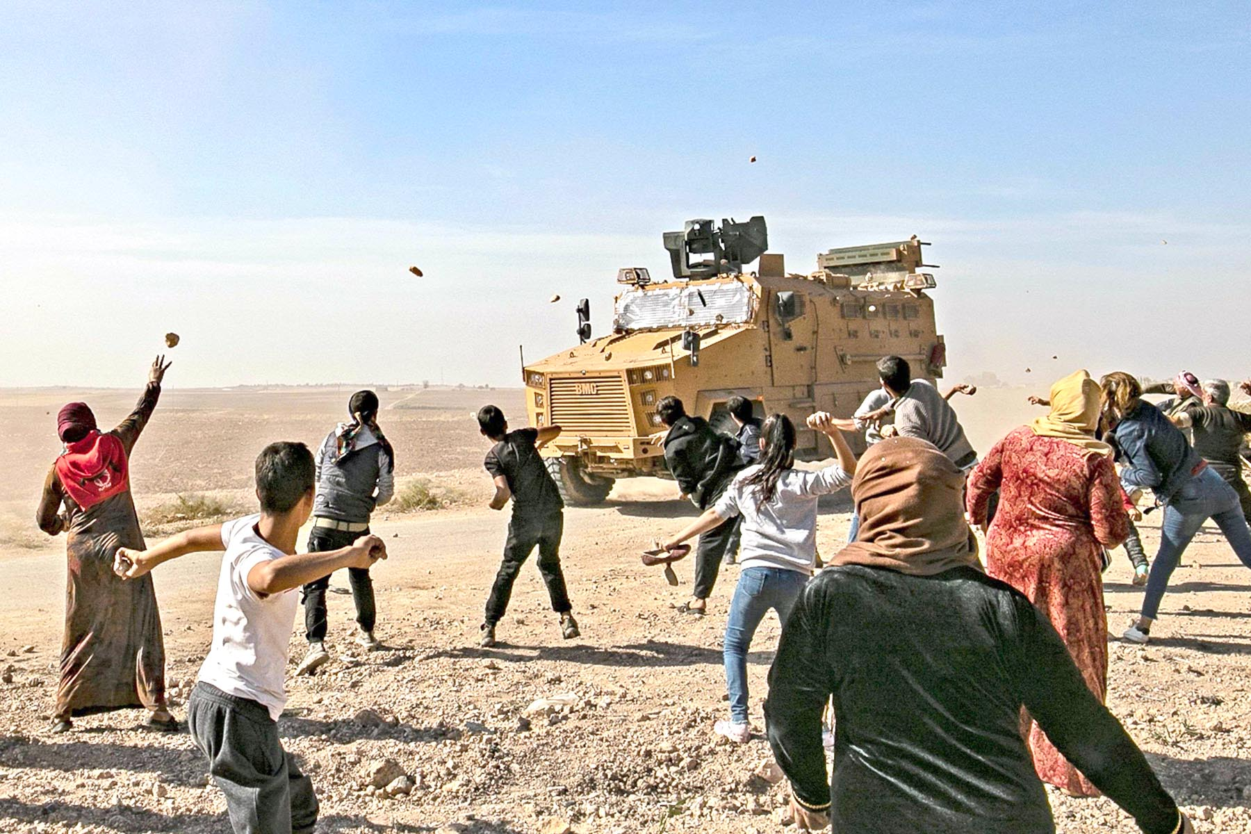 Syrians throw stones towards Turkish military vehicles during an army patrol near the town of Darbasiyah in Syria's north-eastern Hasakah province, November 11. (AFP)
