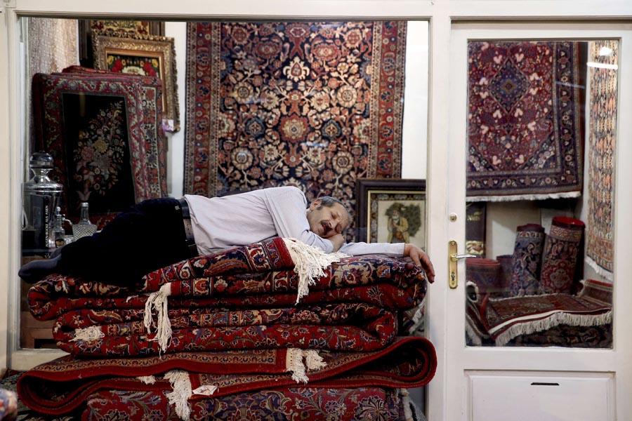 An Iranian carpet seller takes a nap in the old Bazaar in Tehran, last July. (AP)