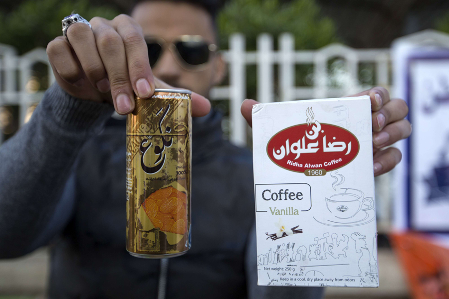 An Iraqi university student shows locally-made coffee and soft drink, during a rally to show support for local products and to encourage the boycott of imported Iranian goods, in Basra December 8. (AFP)