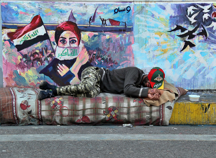 An Iraqi anti-government protester rests during a sit-in at Tahrir Square in Baghdad, December 4. (AP)