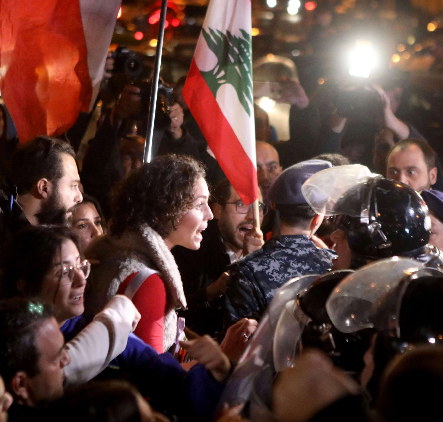Lebanese anti-government protesters scuffle with riot police on the eastern end of the Ring Bridge in Beirut, December 4. (AFP)