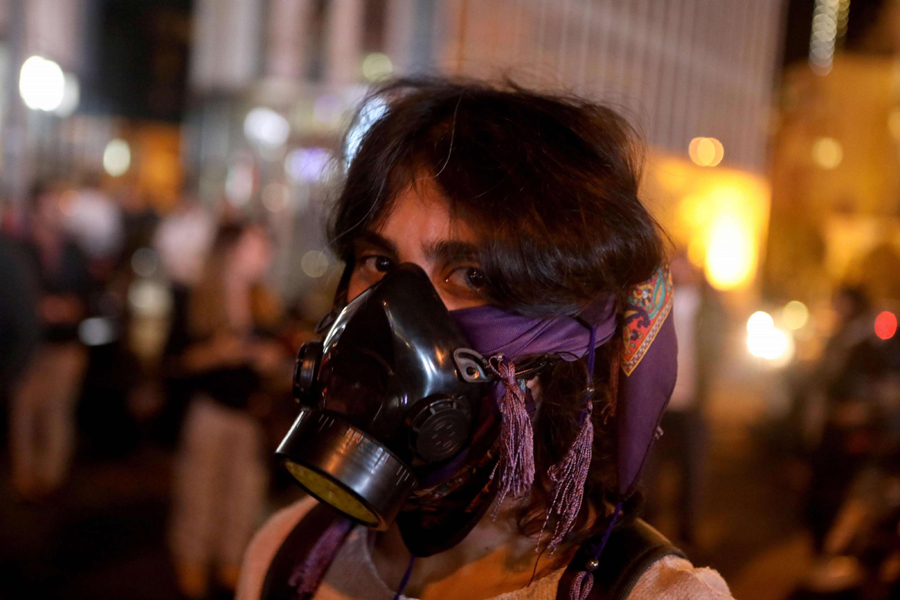 A Lebanese anti-government protester wears a gas mask in Beirut, December 4. (AFP)