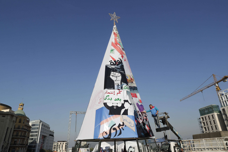 Lebanese anti-government protesters erect a Christmas tree made of protest banners in Beirut's Martyr Square, December 21. (AFP)