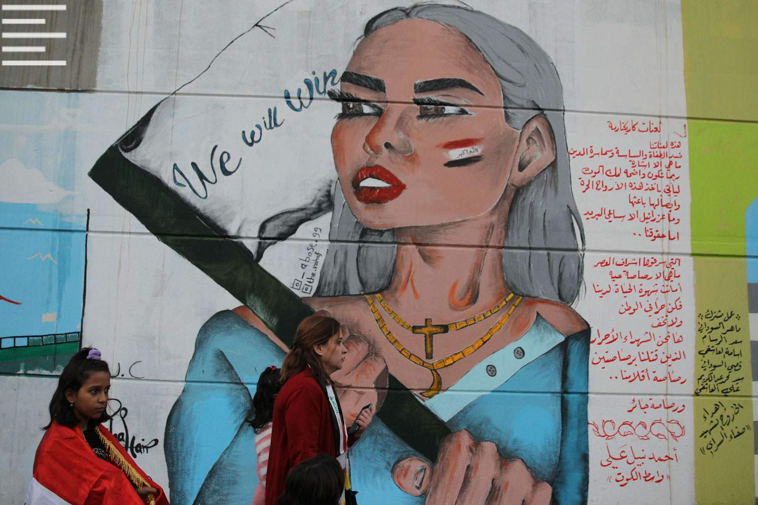 Iraqi protesters walk past a mural bearing a portrait of a Christian woman with the Iraqi national flag painted on her cheek in Baghdad's Tahrir square, November 21. (AFP)