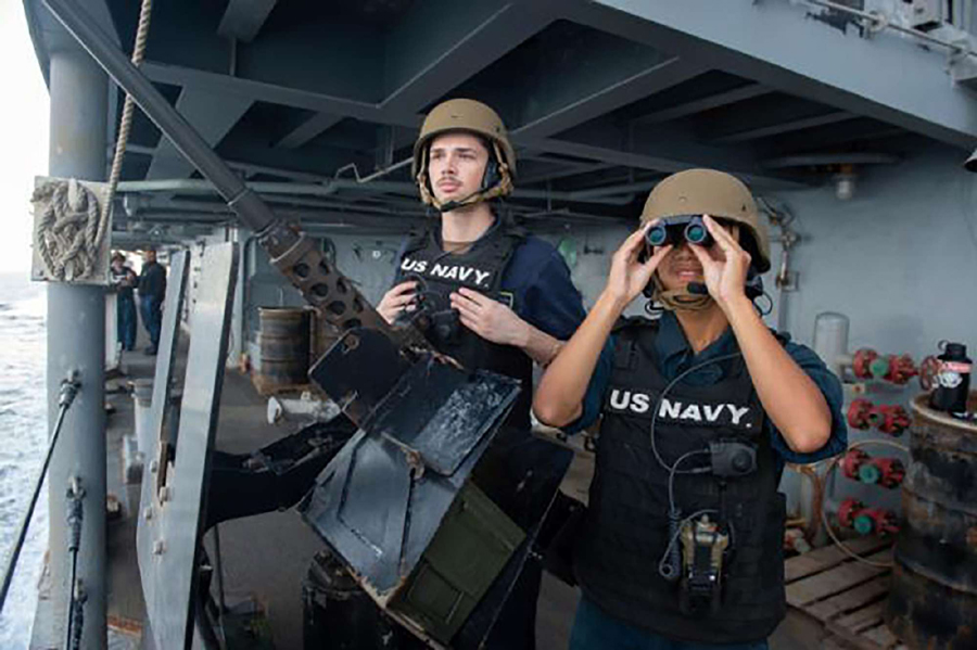 US Navy members stand guard on aircraft carrier USS Abraham Lincoln as it transits the Strait of Hormuz, November 19. (US Navy via AP)