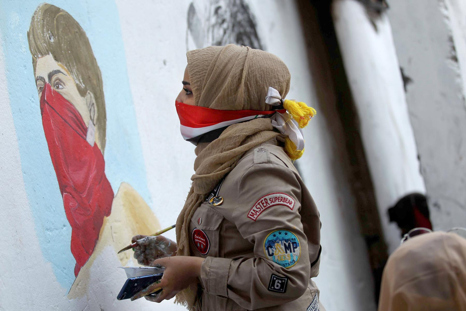 An Iraqi protester paints on a concrete barrier on al-Rasheed Street in Baghdad, December 5. (AFP)