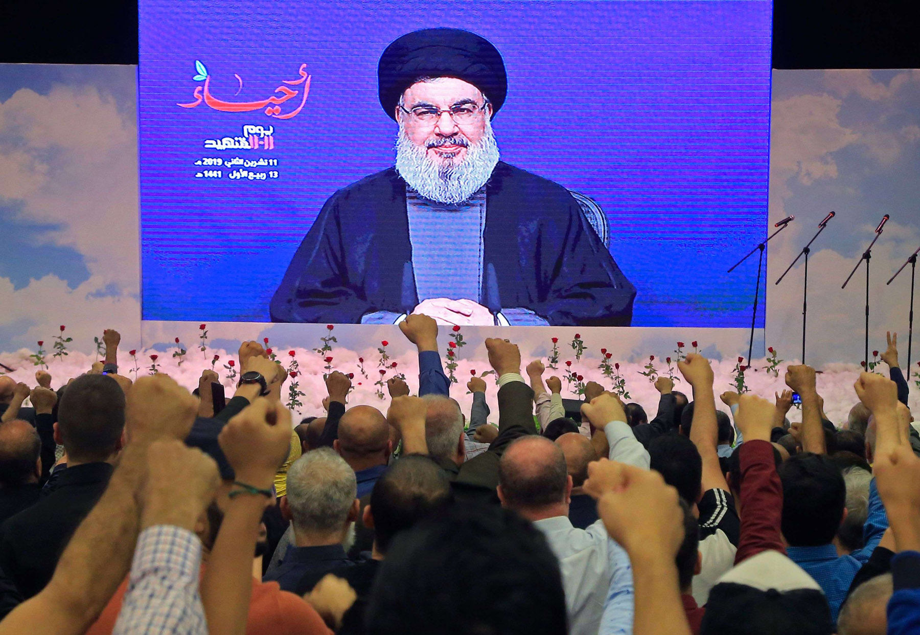 Lebanese Hezbollah leader Hassan Nasrallah speaks to supporters through a giant screen in the capital Beirut's southern suburb. (AFP)
