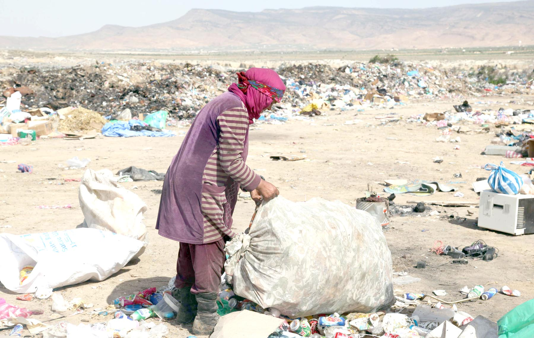 Tough lives. A Tunisian woman sifts through garbage at a landfill in a poor district of Tunisia's central city of Kasserine.      (AFP)