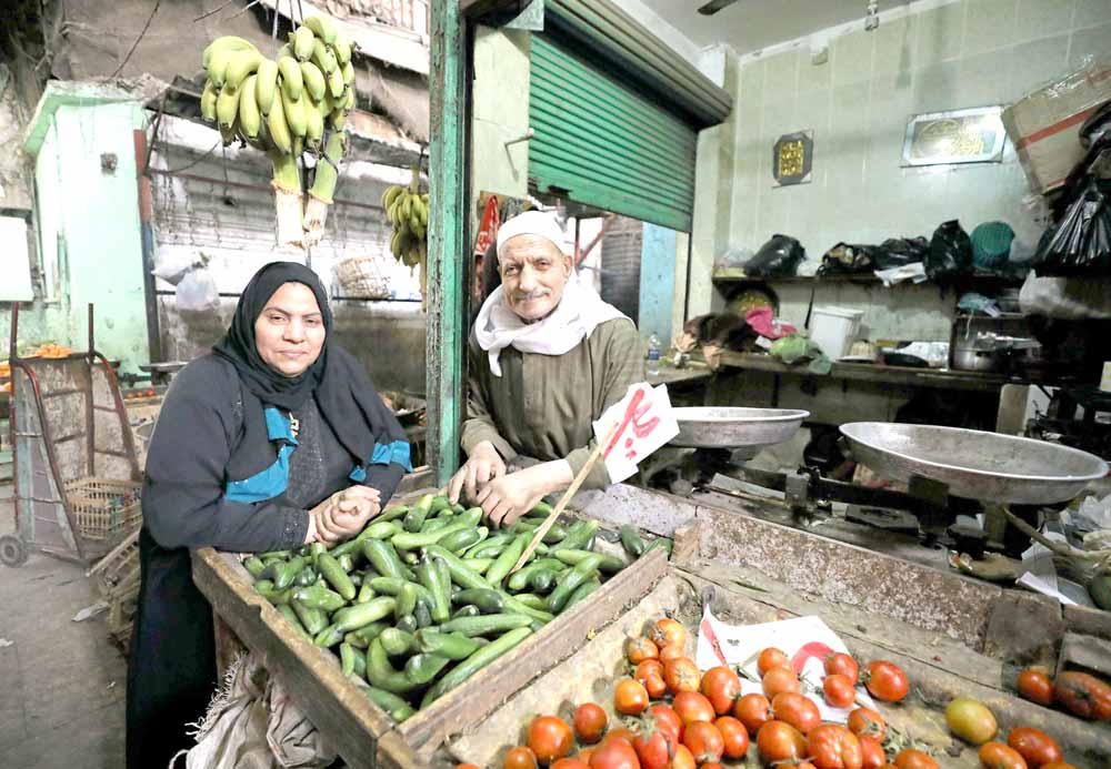 An Egyptian man and his wife pose at their vegetable shop in Cairo.     (Reuters)