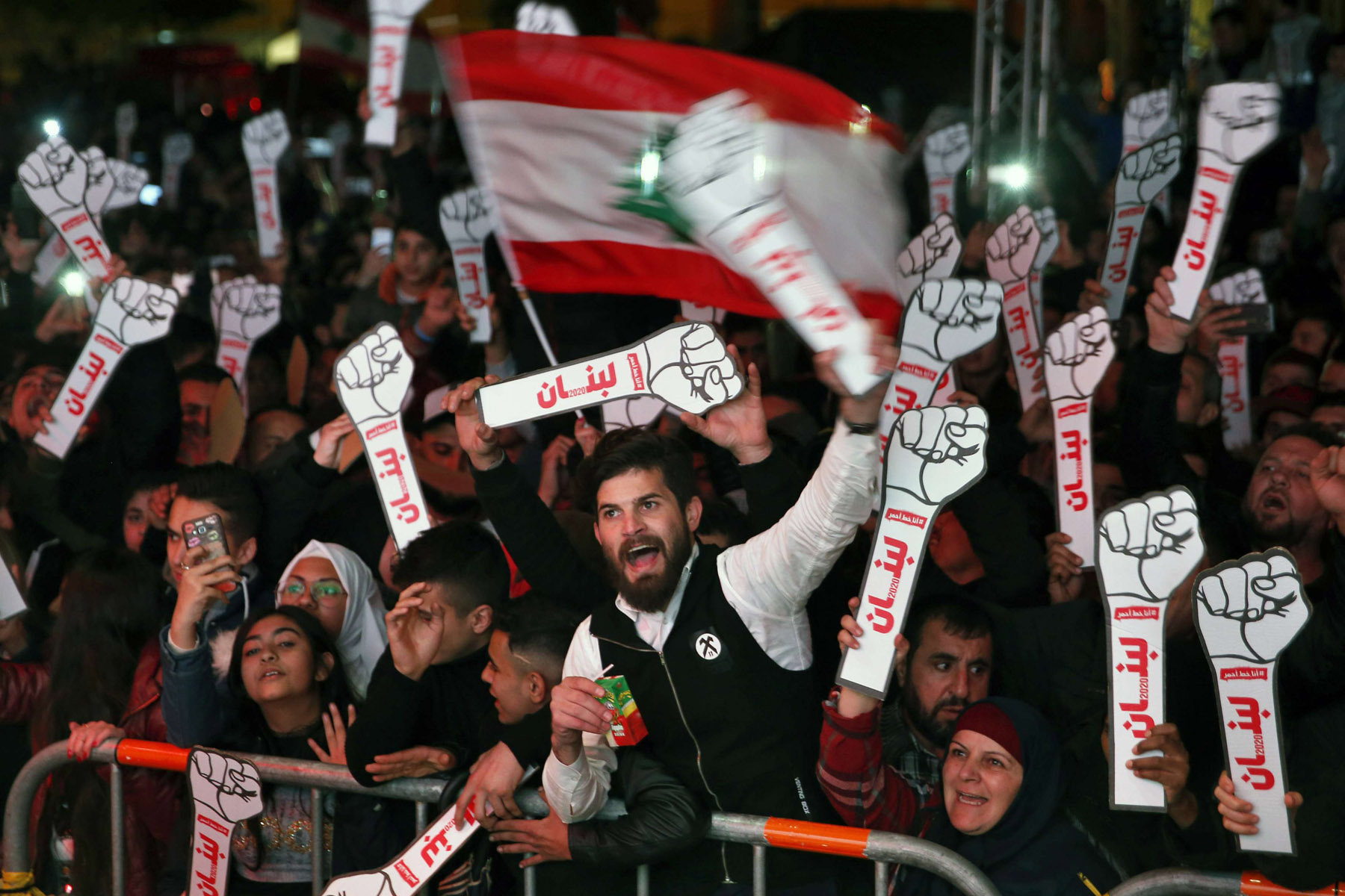 "Peaceful yet defiant. Anti-government protesters chant slogans as they hold clenched fists with an Arabic word that reads ""Lebanon"" during the New Year's celebrations in Martyrs' Square in Beirut, January 1. (AP)"