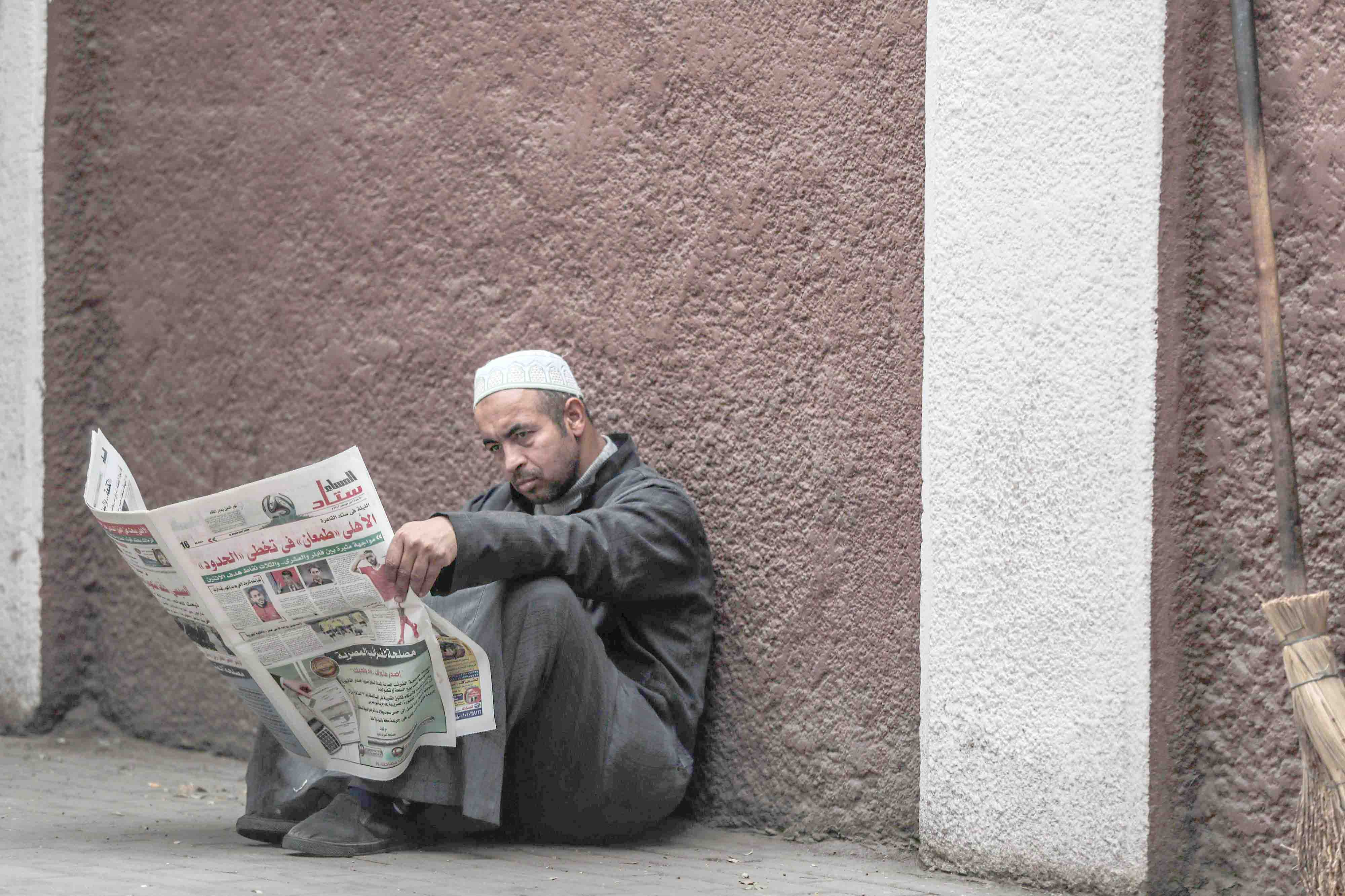 A man reads a newspaper on a sidewalk in the Zamalek district of western Cairo. (AFP)