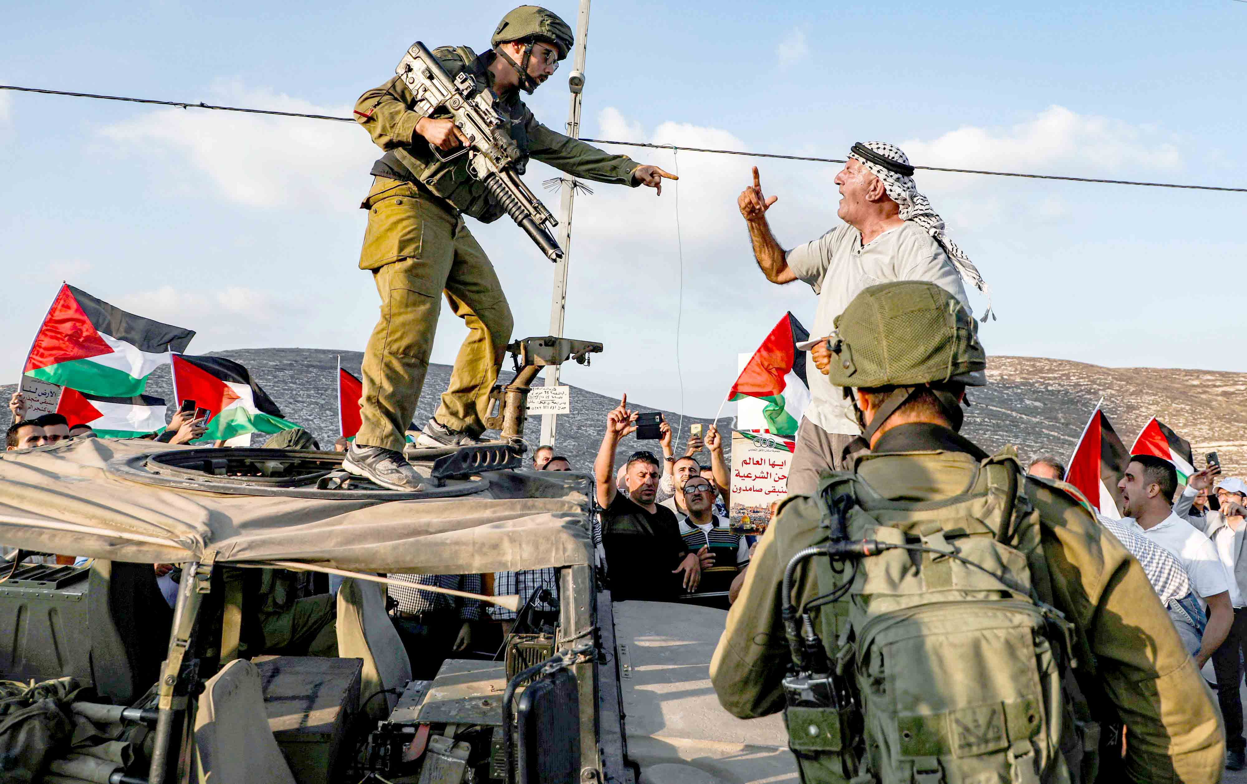 A Palestinian protester yells at an Israeli soldier as he confronts him atop an Israeli army vehicle during a protest near the Palestinian village of Naqura, last September.(AFP)