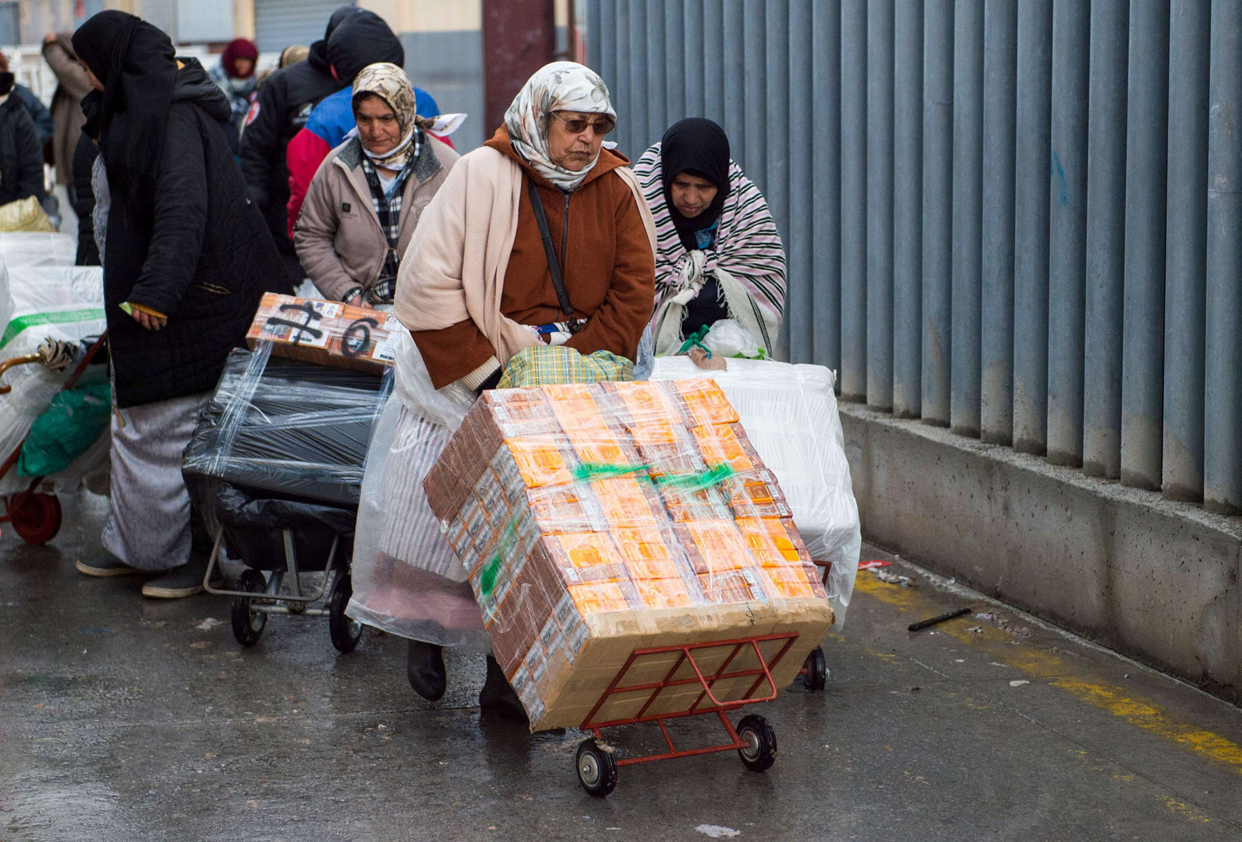 Heavy loads. Female Moroccan porters use trolleys to transport bundles of goods across Tarajal II border from Spain's North African enclave of Ceuta into Morocco.  (AFP)