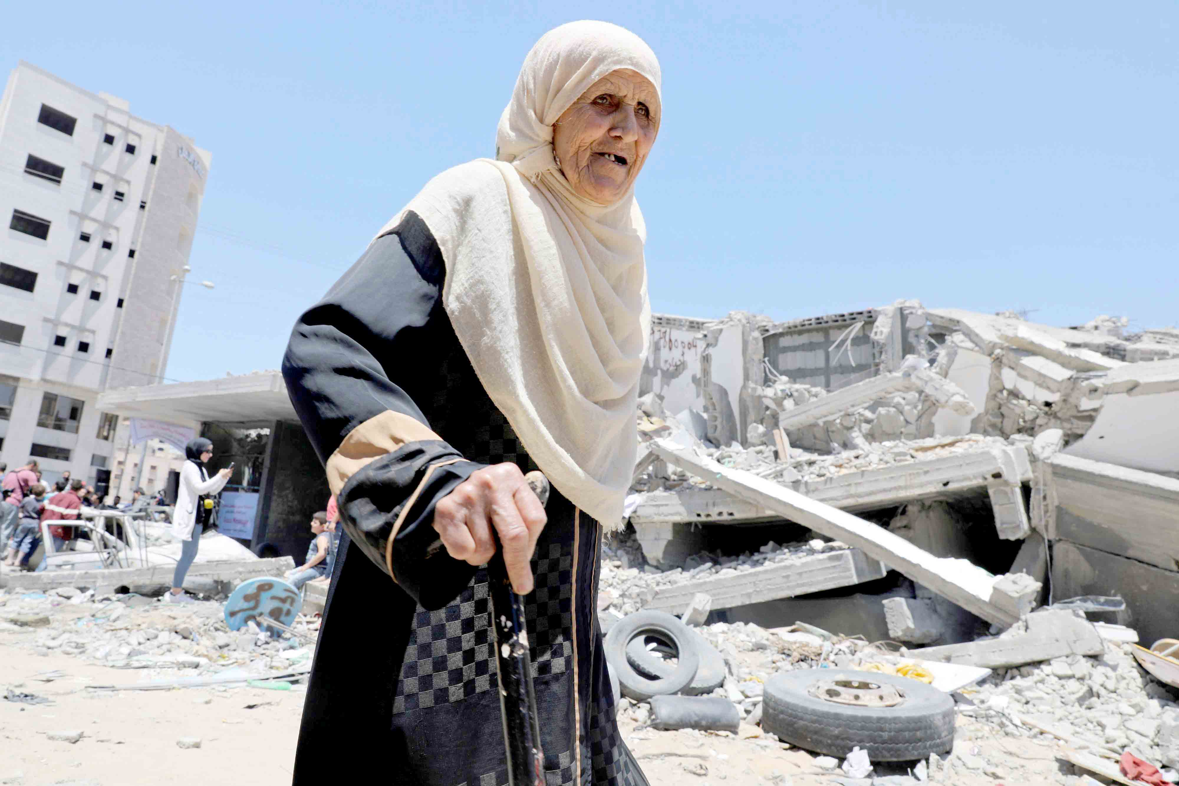 A Palestinian woman walks past the rubble of a building destroyed by Israeli air strikes in Gaza City, last May.(Reuters)