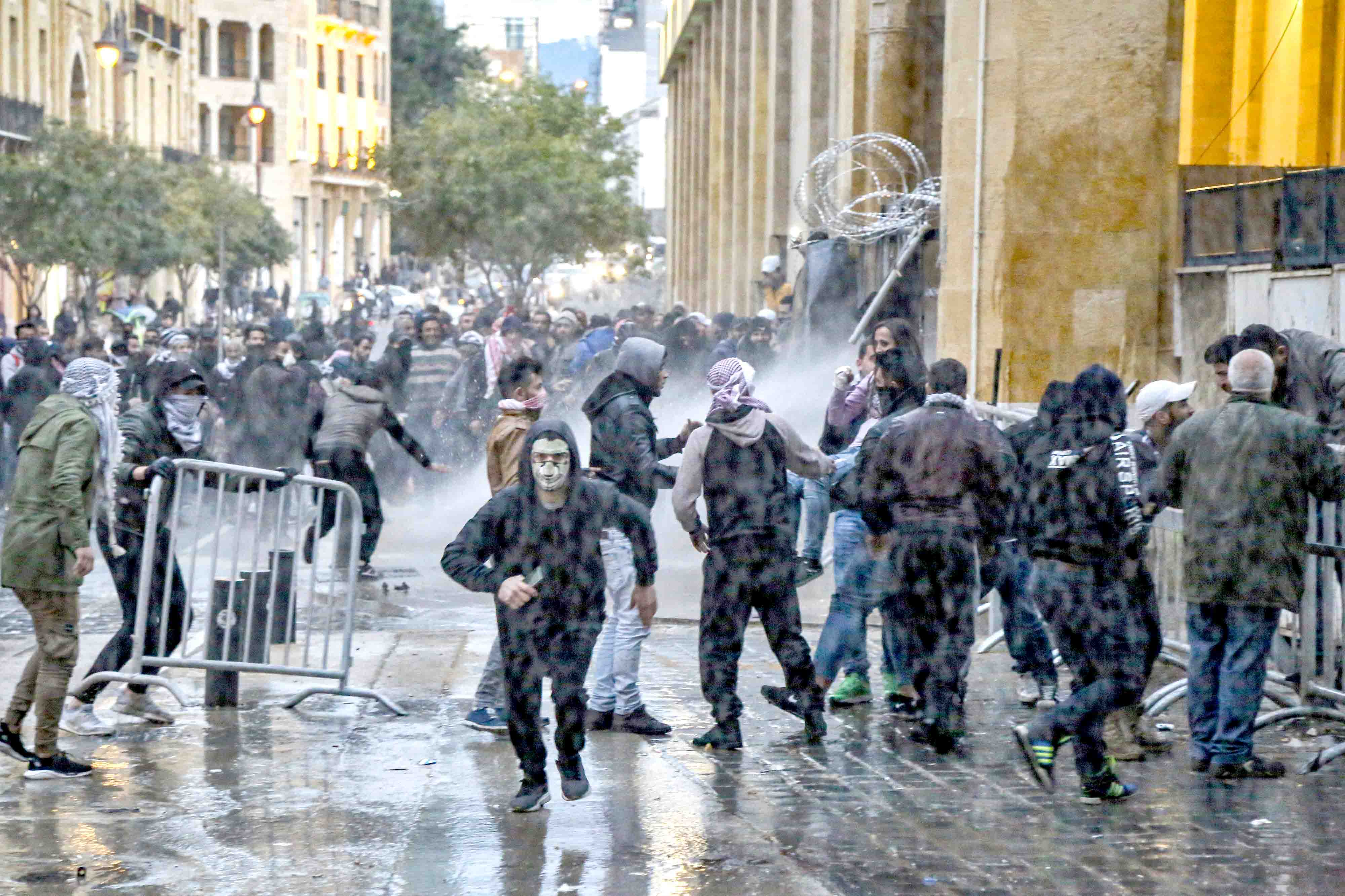 Anti-government protesters clash with riot police during a demonstration against the new government near the parliament building in Beirut, January 22. (DPA)