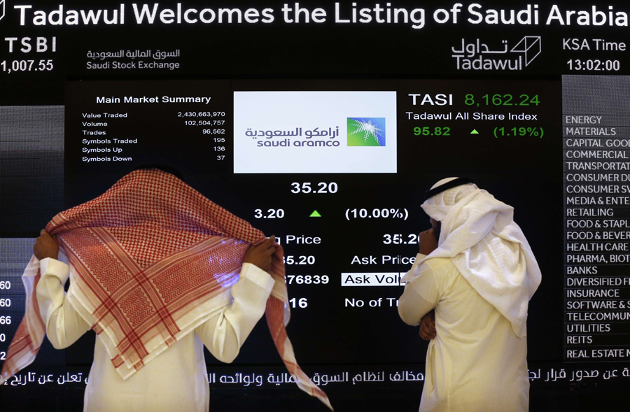 $2 trillion valuation. Saudi officials watch the stock market screen displaying Saudi state-owned oil company Aramco, in Riyadh. (AP)