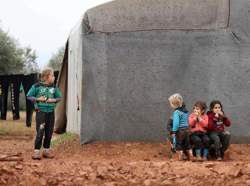 Syrian children, who fled air Assad regime/Russian strikes in their hometown, are pictured near tents at an informal camp for displaced people in Syria's Idlib province, January 7. (AFP)