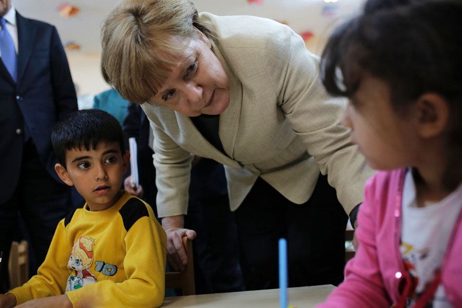 German Chancellor Angela Merkel talks with Syrian refugee children at a preschool, during a visit to a refugee camp on the Turkish-Syrian border in Gaziantep. (AFP)