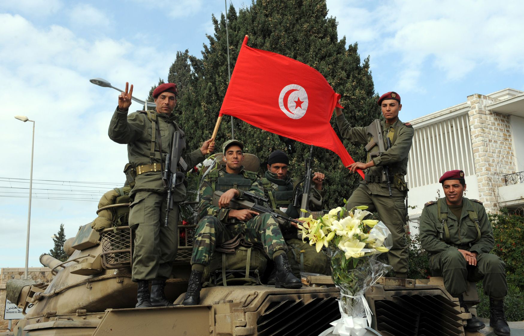 Nine years ago. Tunisian soldiers holding a Tunisian flag stand guard in their tank in Carthage, January 21, 2011. (AFP)