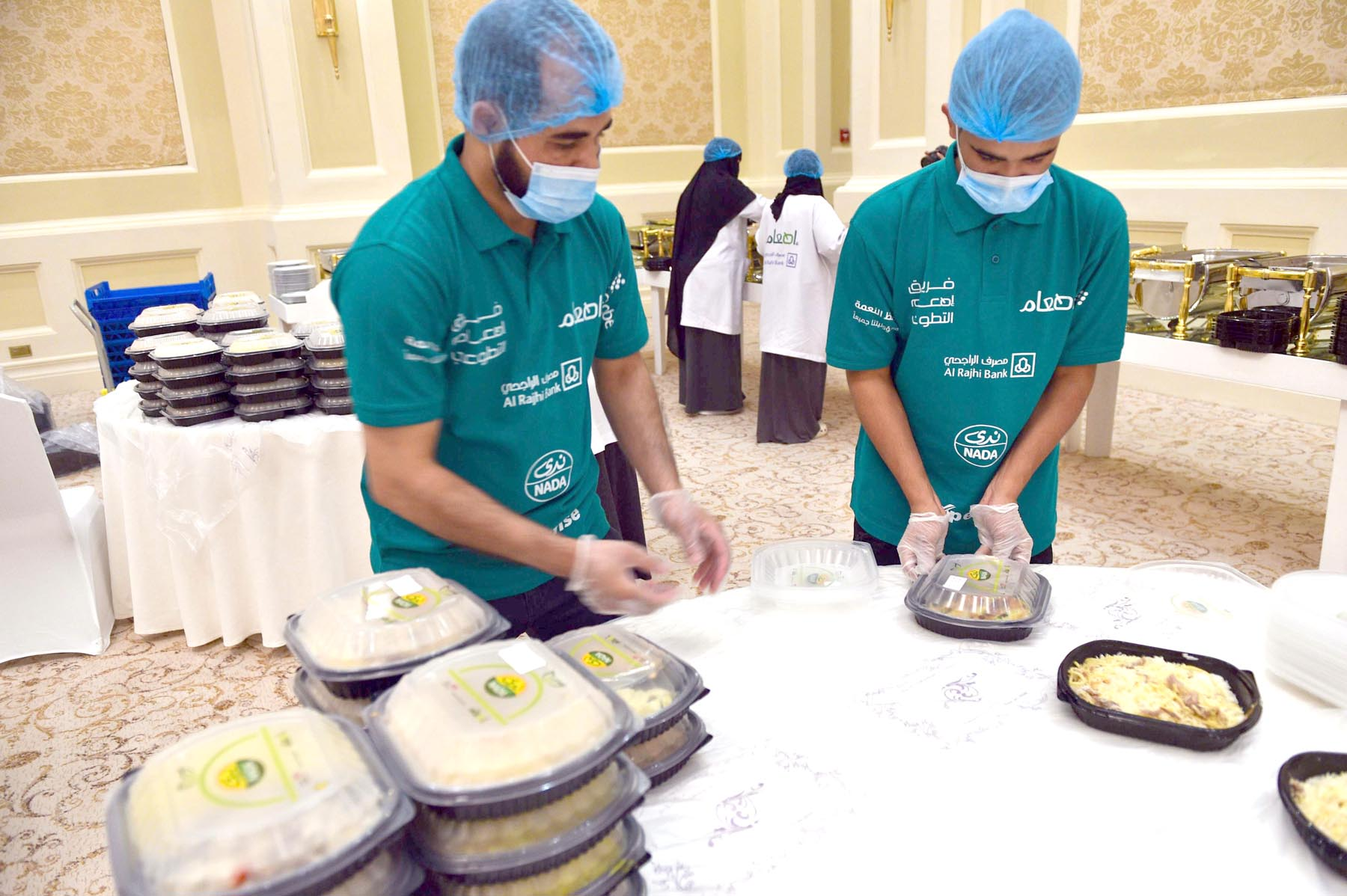 Saudi volunteers, with the Saudi Food Bank or Etaam, pack leftovers into boxes.   (AFP)