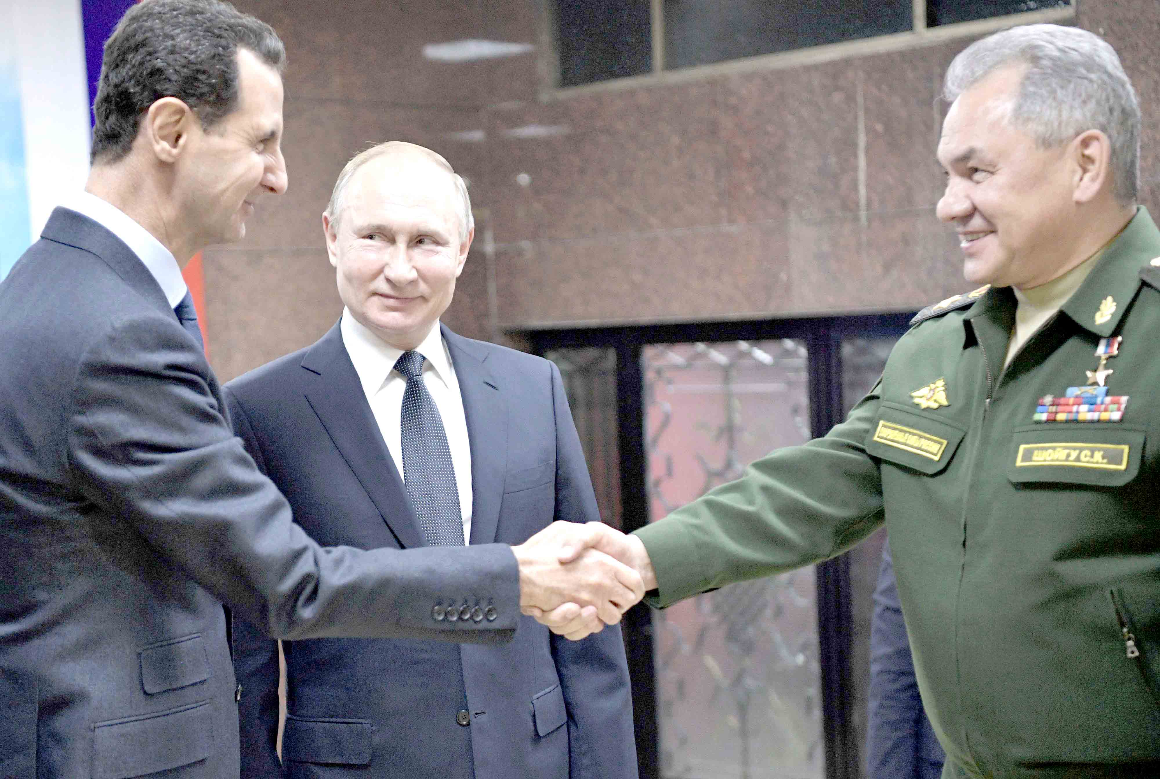 Shielding Syria. Russian President Vladimir Putin (C), Defence Minister Sergey Shoigu (R) and Syrian President Bashar Assad meet in Damascus, January 7.(Reuters)