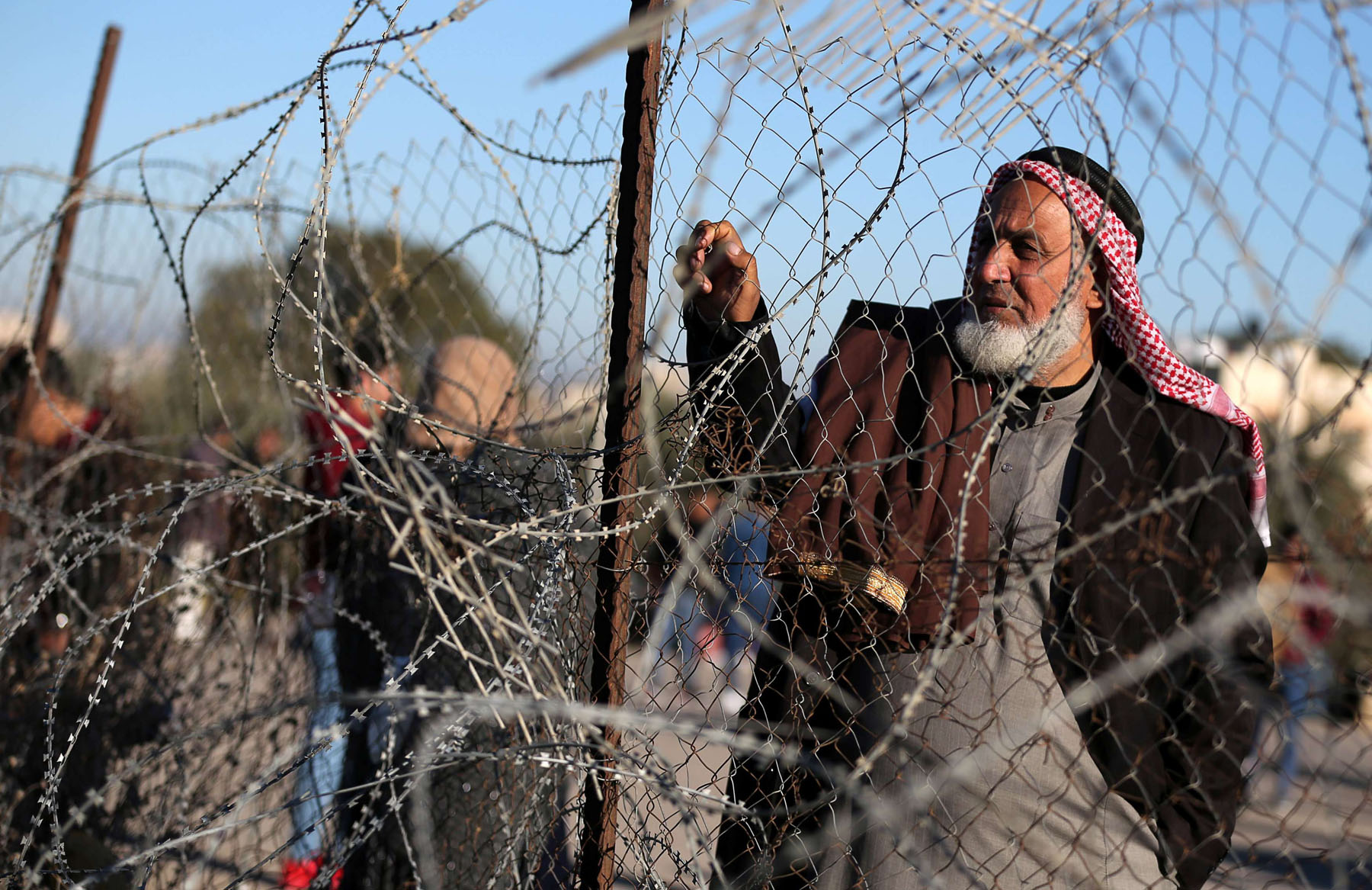 Out of focus. A Palestinian man stands by a fence as he waits for a travel permit to leave Gaza through the Rafah border crossing with Egypt. (Reuters)