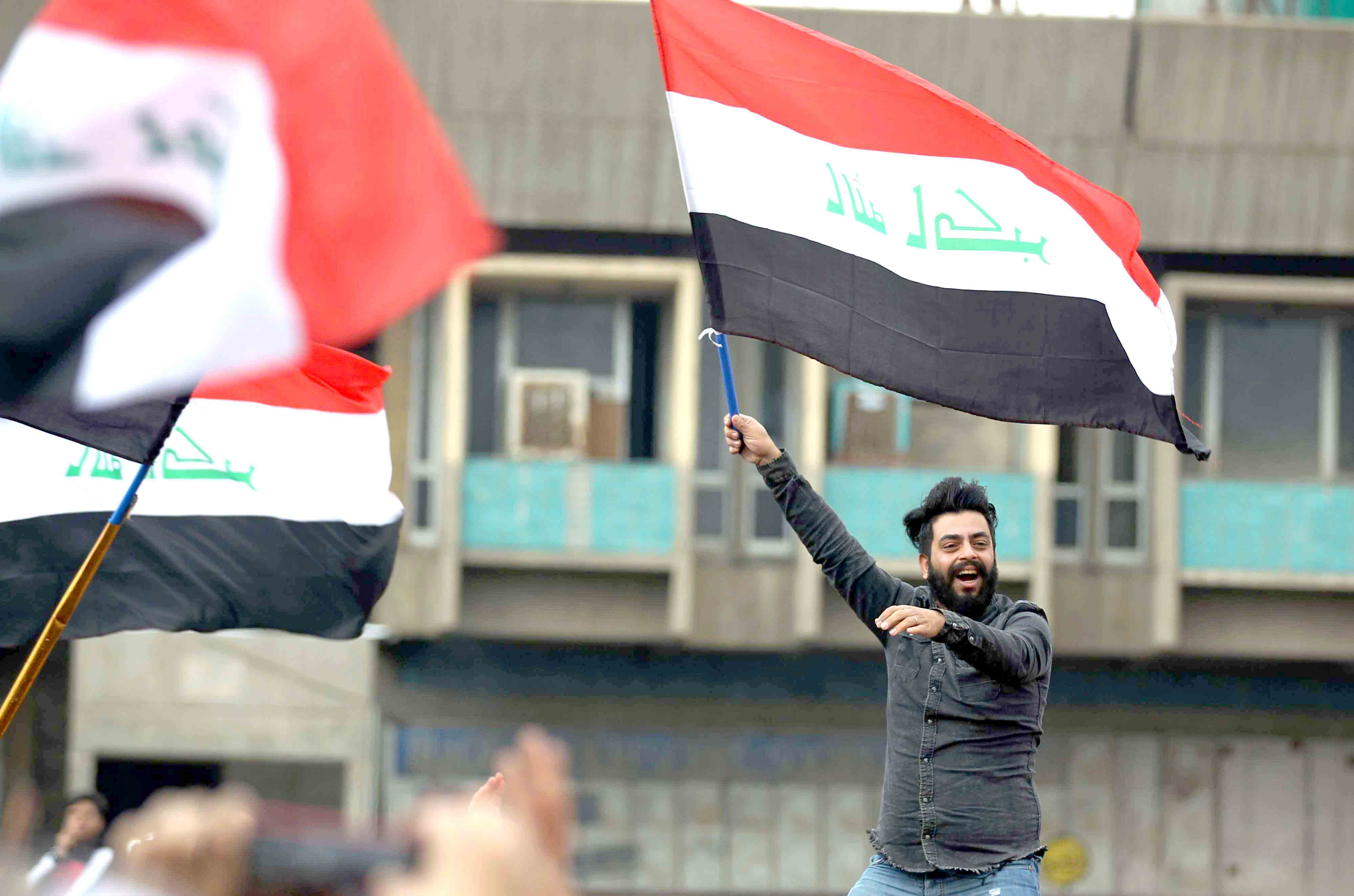 An Iraqi anti-government demonstrator waves the national flag as he protests in Baghdad's Tahrir square, January 10. (AFP)