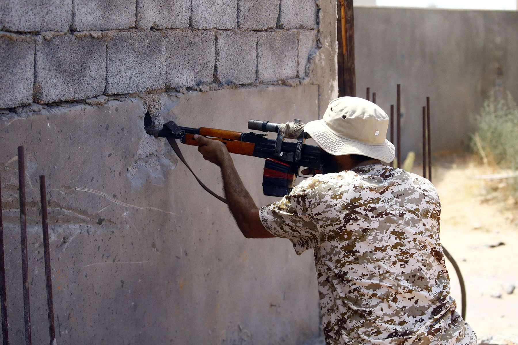 A fighter loyal to the Turkey-backed Government of National Accord fires shots during clashes with the Libyan National Army in Tripoli's suburb of Ain Zara. (AFP)