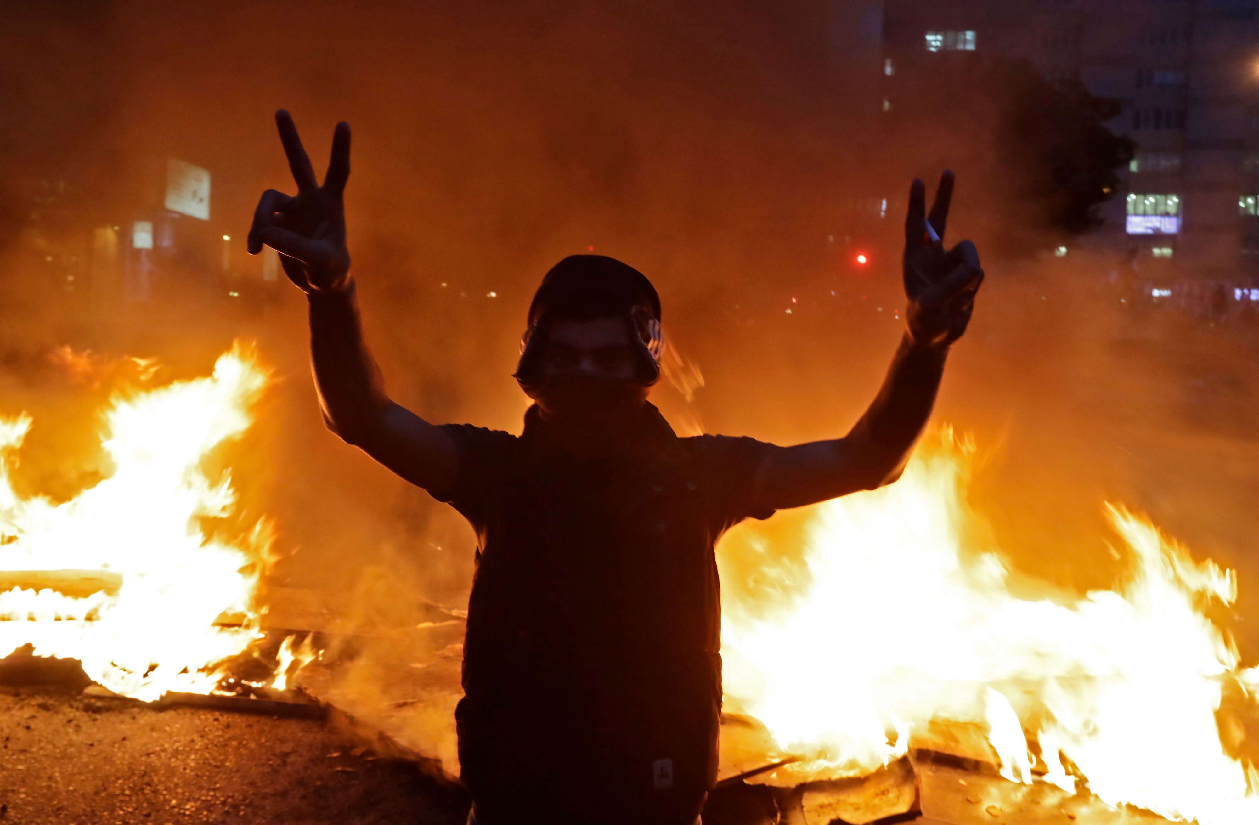 Violent drift. A Lebanese anti-government protester flashes the victory sign in front of a burning barricade in Beirut, January 15. (AFP)