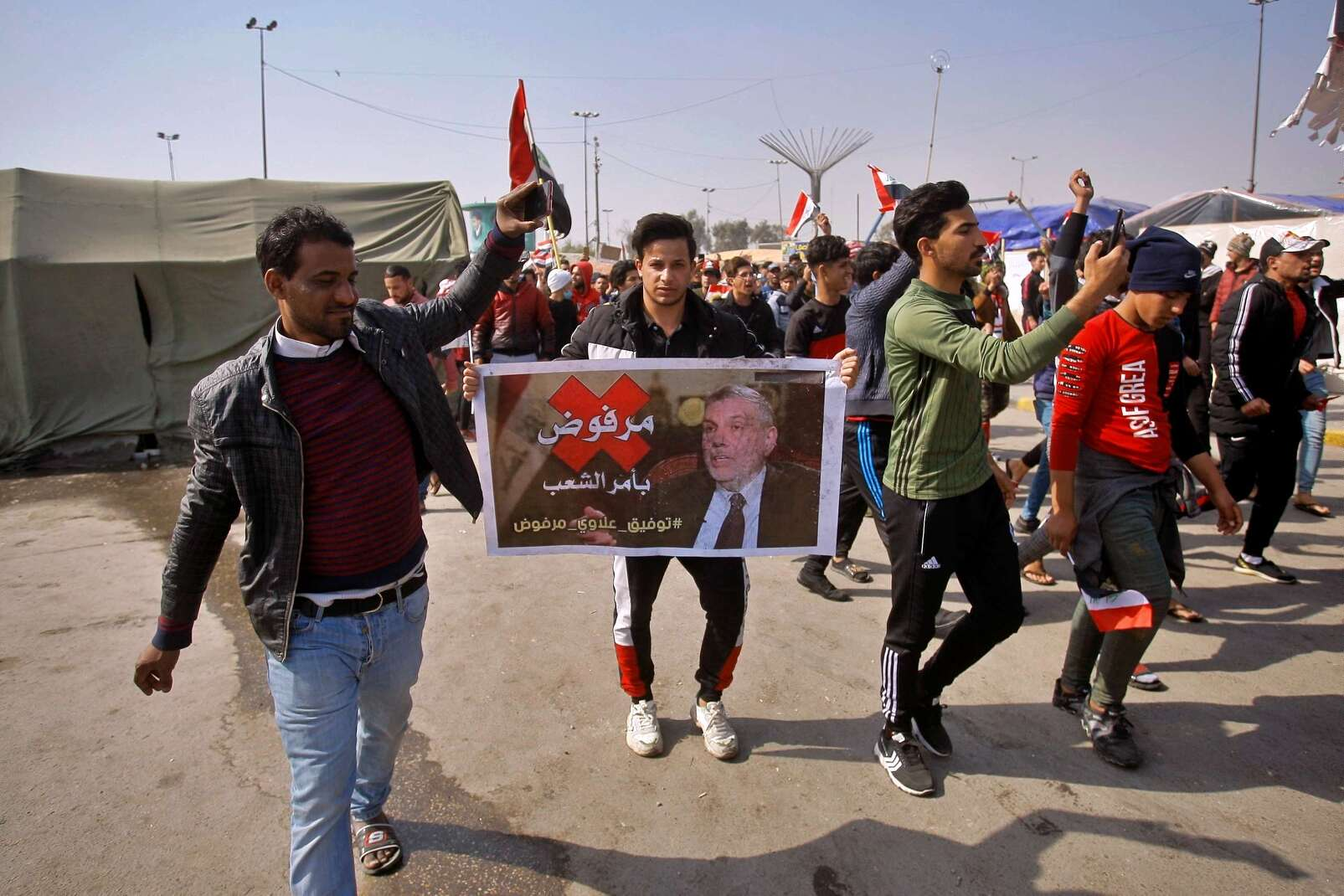 "Protesters chant slogans while holding a poster of newly-appointed Prime Minister Mohammed Allawi with Arabic that reads, ""Rejected by the people,"" during a demonstration in Najaf, Iraq, Thursday, Feb. 6, 2020. (AP)"