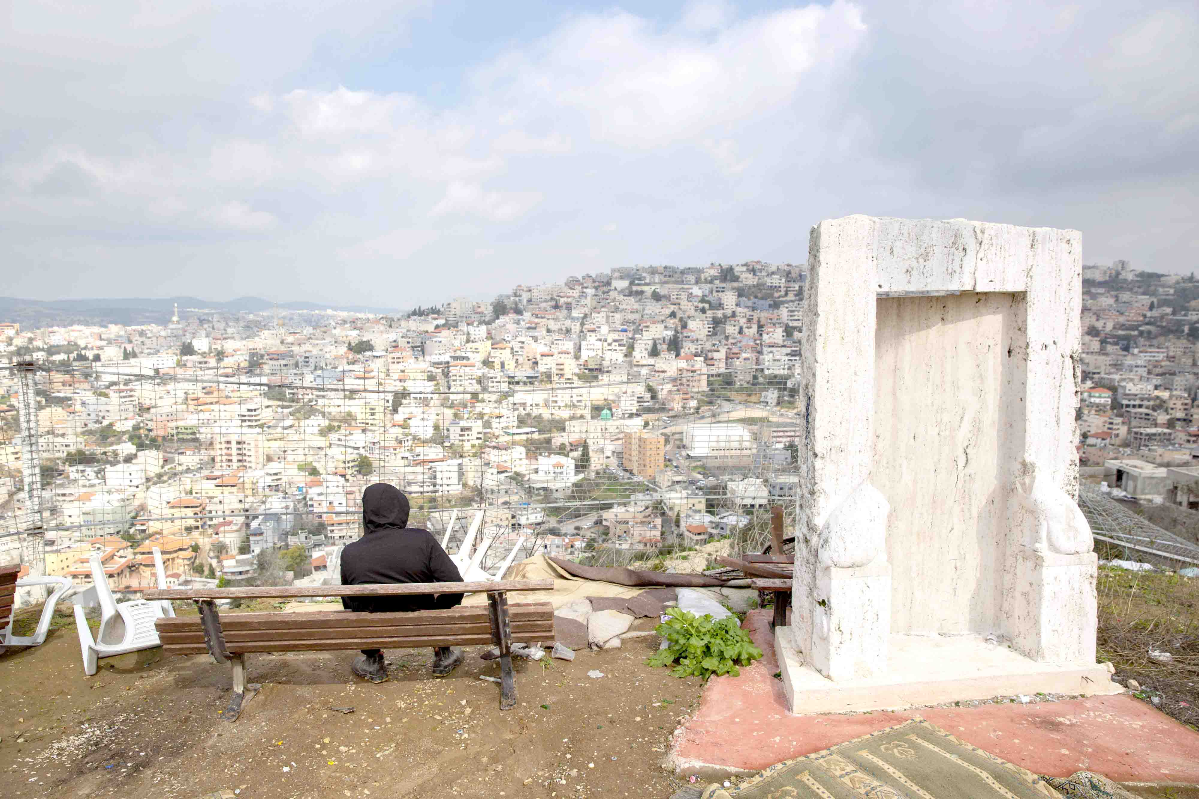 An Israeli Arab youth sits at a view point overlooking the Israeli Arab town of Umm al-Fahm.(AP)