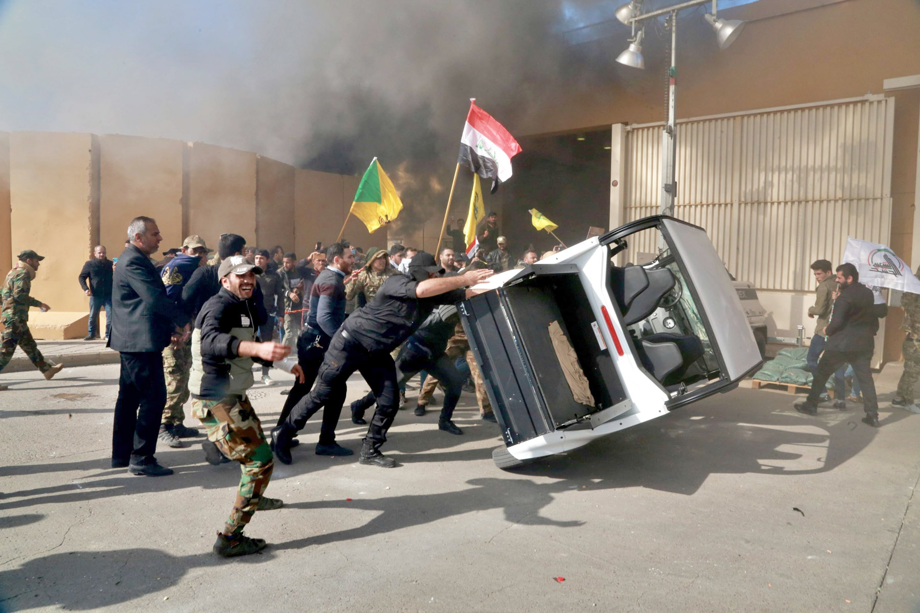 Supporters of Iran-backed Popular Mobilisation Forces damage property inside the US Embassy compound in Baghdad, last December. (AP)