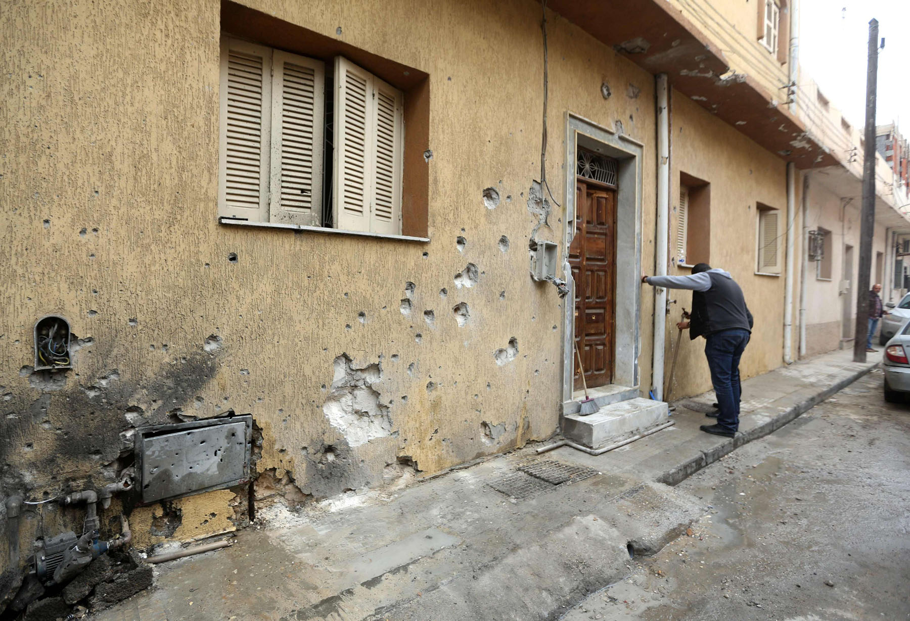 A man checks a shell-pocked wall in a street that was reportedly hit during shelling by forces loyal to Libyan National Army in Tripoli's Batata neighbourhood, February 13. (AFP)