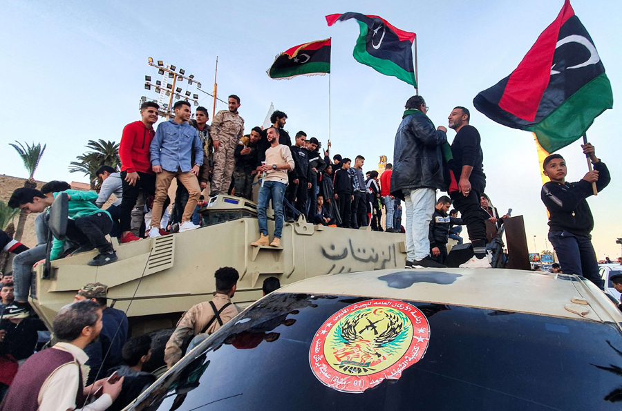 "Libyans stand with their national flags above armoured military vehicles of forces loyal to the UN-recognised ""Government of National Accord"" during a celebration in Tripoli, January 31. (AFP)"